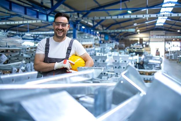 Улыбающийся заводской рабочий в каске стоит на производственной линии завода