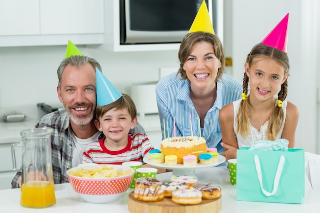 Smiling family celebrating a birthday together in kitchen
