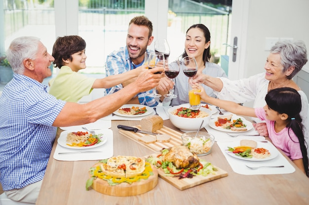 Smiling family clinking with drink glasses