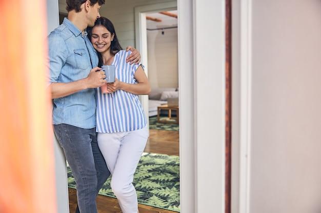 현대 거실에 서있는 동안 손에 커피 잔을 들고 웃는 가족 부부