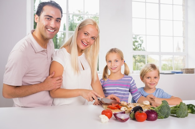 Smiling family cutting vegetables together