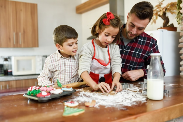 Sorridente famiglia decorare biscotti di natale in cucina
