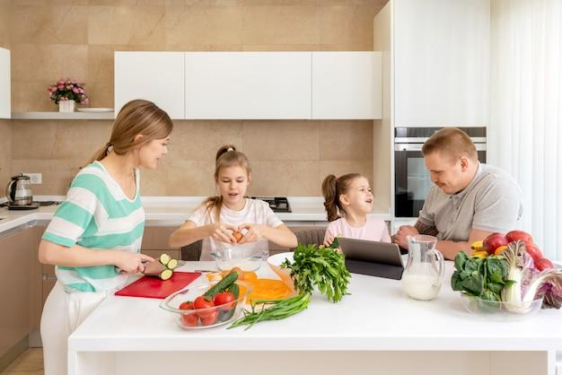 笑顔の家族が一緒に台所のテーブルで食事をし、楽しんで、2人の娘を持つ親