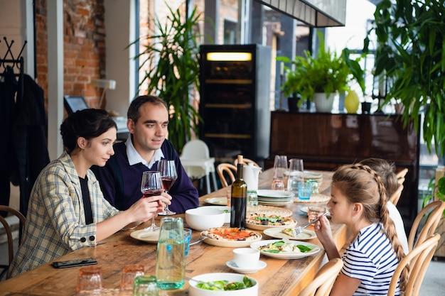 Улыбающиеся семьи обедают вместе на кухне