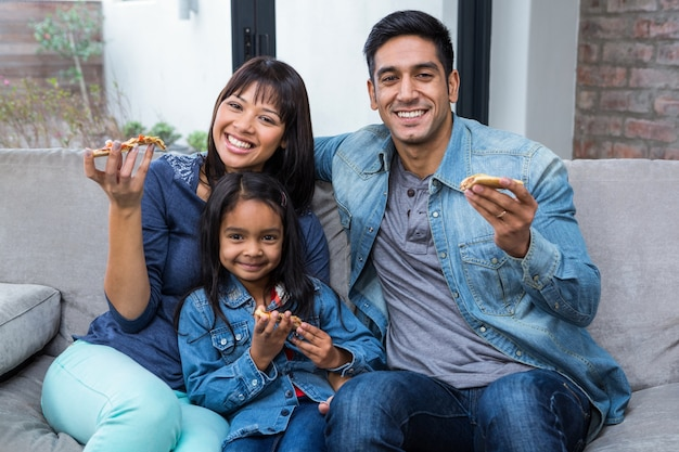 Улыбается семьи едят пиццу на диване