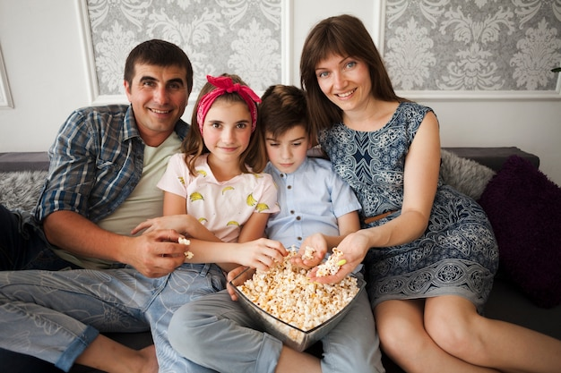 Smiling family holding popcorn and looking at camera while sitting on sofa