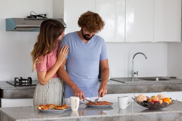 Улыбающаяся семья на кухне готовит и пробует еду