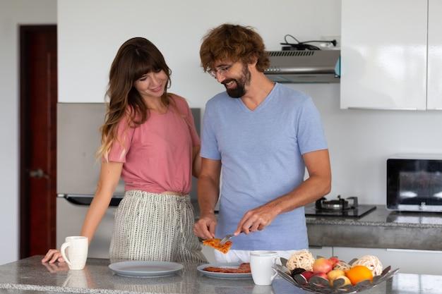 Famiglia sorridente in cucina a preparare e degustare il cibo