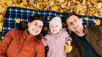 Smiling family lying at autumn park