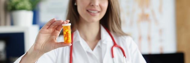 웃고 있는 가정의학 의사가 환자에게 알약 병을 들고 준다