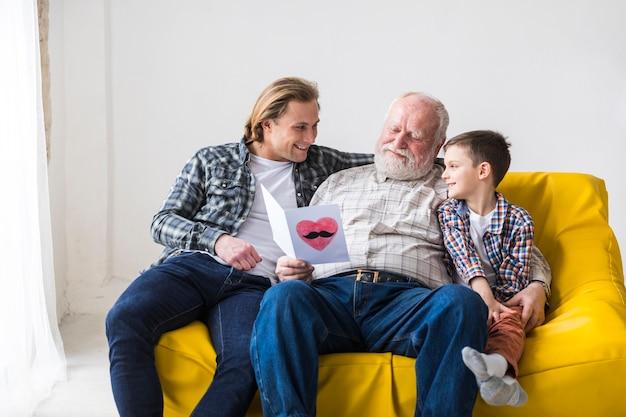 Улыбающаяся семья мужчин обниматься на диване
