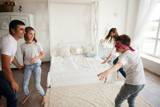 Smiling family playing blind man's buff in bedroom