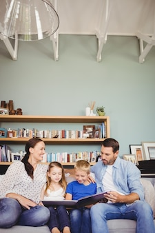 Smiling family reading book while sitting on sofa