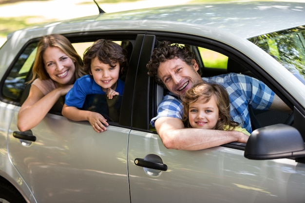 Smiling family sitting in a car