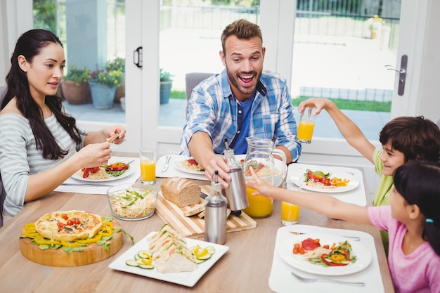 Smiling family sitting at dining table with food