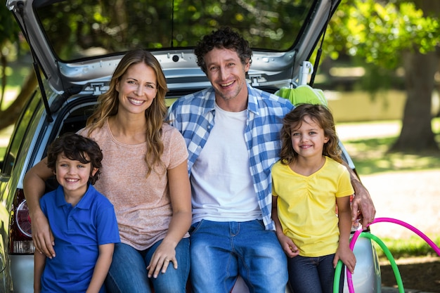 Улыбающаяся семья сидит в багажном отделении