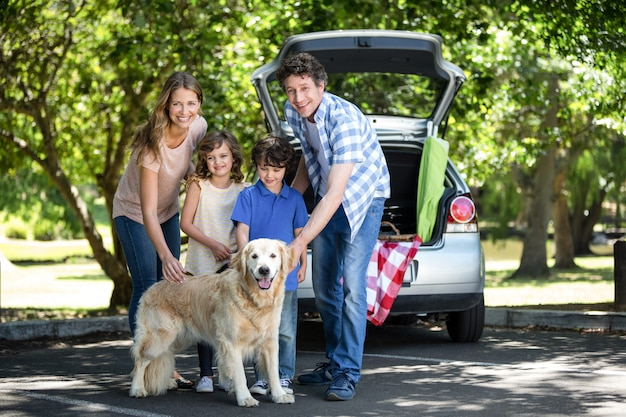 Smiling family standing in front of a car