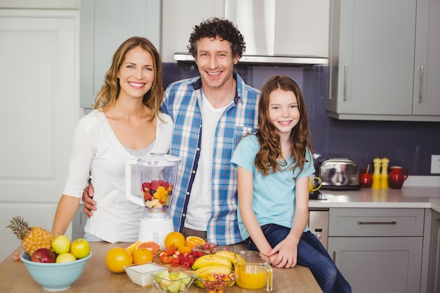 Smiling family standing at table with fruits
