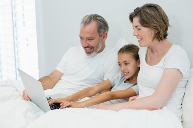 寝室のベッドの上のラップトップを使用して家族の笑顔