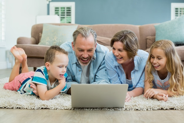 Smiling family using laptop while lying on carpet in living room