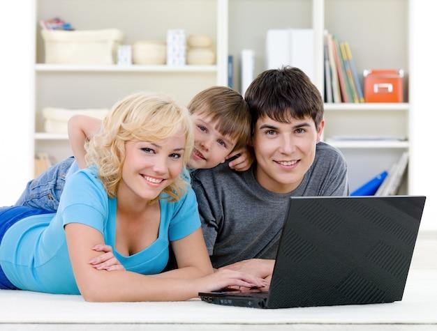 ラップトップを使用して笑顔の家族