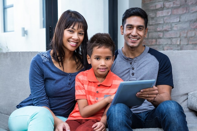 Smiling family using tablet on the sofa