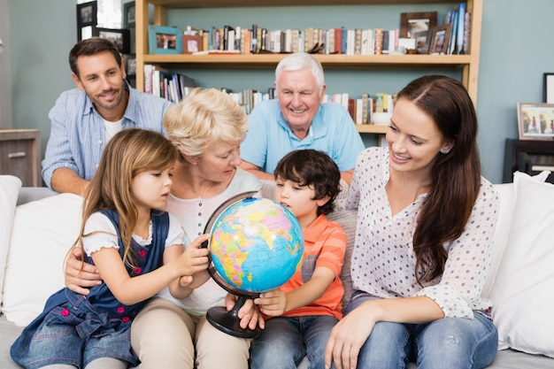 Smiling family with globe while sitting on sofa