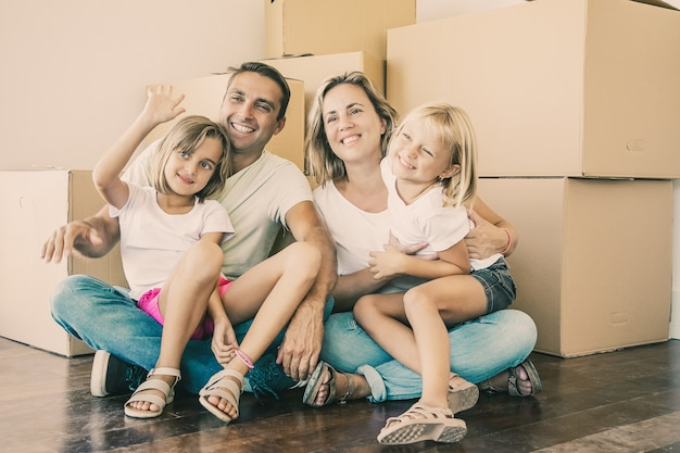 Smiling family with kids sitting on floor near cardboard boxes and relaxing. blonde girl on father legs waving