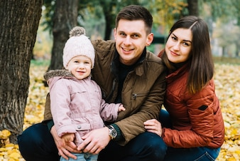 Smiling family with little daughter in autumn park