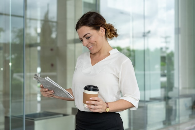 Smiling famous business lady reading article