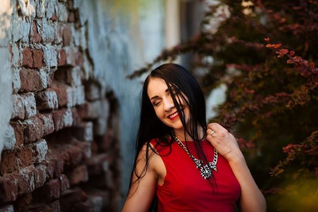 笑顔のファッションの美しさの肖像画。壁に立っている赤いファッションのドレスを着ている巻き毛の美しい女性は目を閉じた