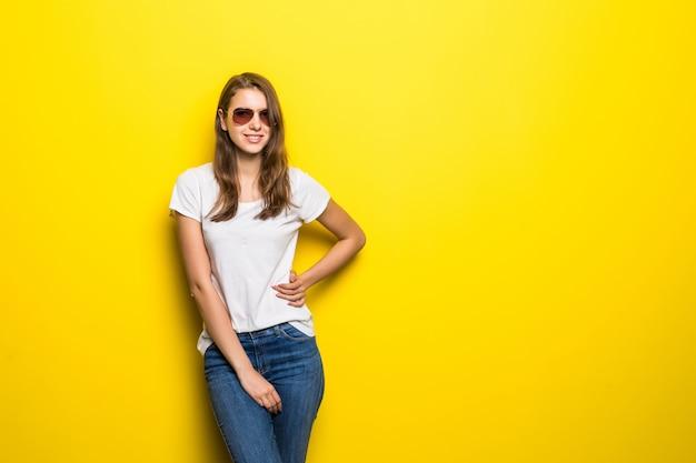 白いtシャツとジーパンで笑顔のファッションの女の子は、黄色のスタジオの背景の前に滞在します。