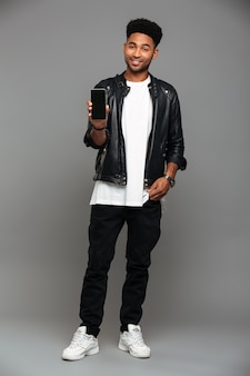 Smiling fashionable african guy standing with hand in his pocket while showing blank mobile screen, looking
