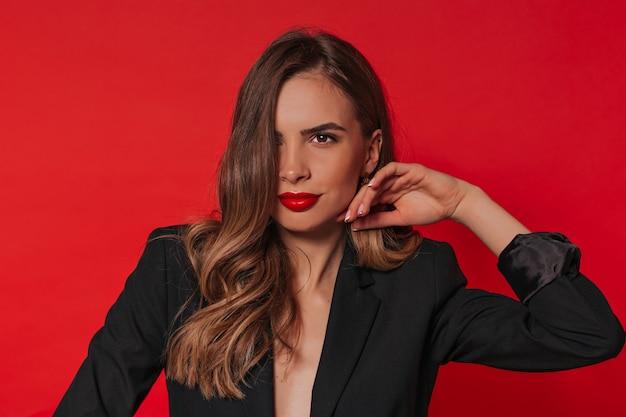 곱슬 밝은 갈색 머리를 가진 유행 유럽 여자를 웃고, 검은 자 켓과 고립 된 위에 포즈 빨간 립스틱을 입고.