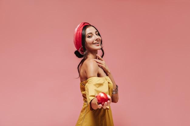 Sorridente signora alla moda con i capelli ricci in bandana rossa, accessori e prendisole giallo brillante con mela rossa e guardando davanti