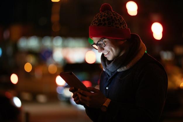 彼の携帯電話を使って眼鏡でファッショナブルな男を笑って