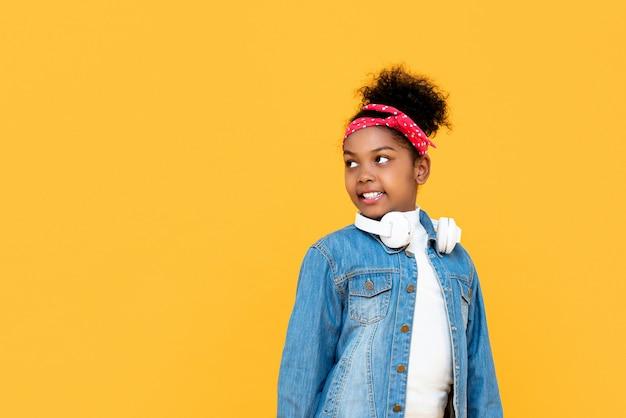 Усмехаясь модная смешанная гоненная африканская девушка смотря в сторону copyspace