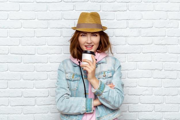 Smiling fashionable woman drinking coffee