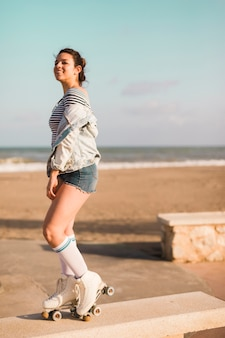 Smiling fashionable young woman standing on bench at beach