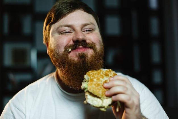 웃는 뚱뚱한 남자는 tv 세트 전에 앉아 햄버거를 먹는다