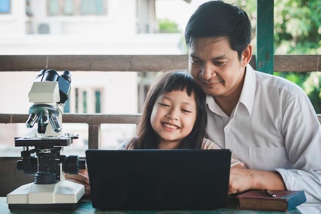 노트북과 현미경으로 집에서 배우는 아버지와 딸 미소. 코로나 바이러스 또는 코로나 19 확산 학교 폐쇄