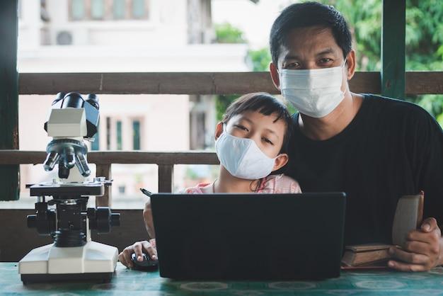 웃는 아버지와 딸 얼굴 마스크를 쓰고 노트북과 현미경으로 가정에서 학습. 코로나 바이러스 또는 covid-19 발발 학교 폐쇄