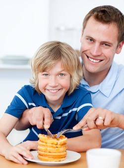 笑顔の父と彼の息子はワッフルを食べる