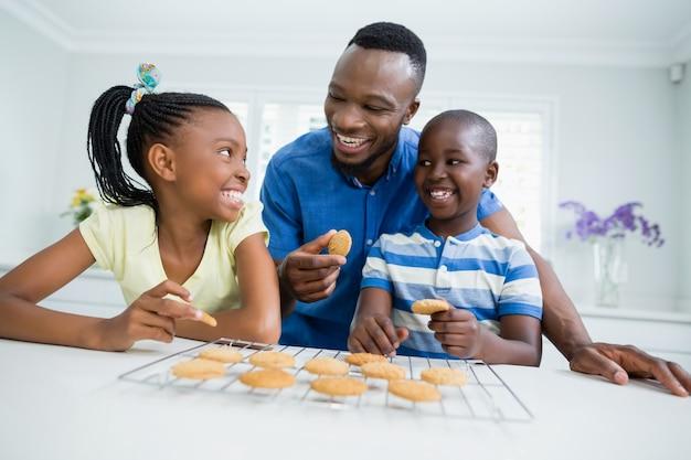 父と子供たちが家でクッキーを食べて笑顔