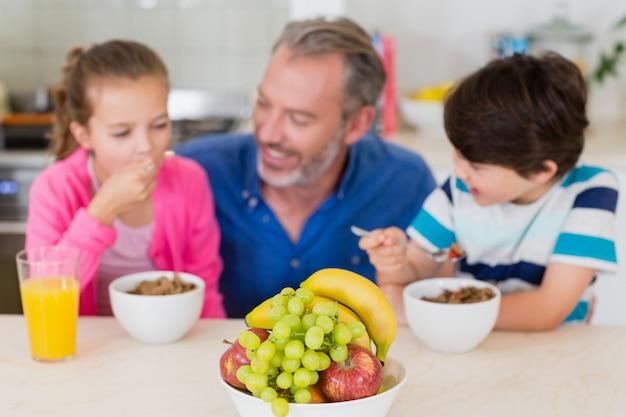 Улыбающийся отец и дети завтракают на кухне