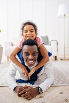 웃고 있는 아버지와 어린 딸이 거실에서 포즈를 취하고 있습니다. 아빠와 여자 아이가 함께 집에서 여가, 좋은 관계