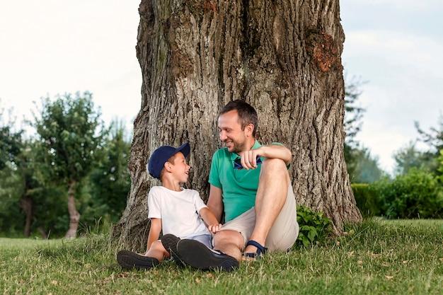 오래 된 나무 아래 잔디에 앉아 웃는 아버지와 아들 남자와 소년 자연에서 휴식