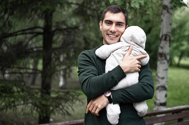 Улыбающийся отец брюнетка в зеленой куртке с ребенком на руках на прогулке в парке с копией пространства