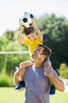彼の息子を肩に乗せて笑顔の父