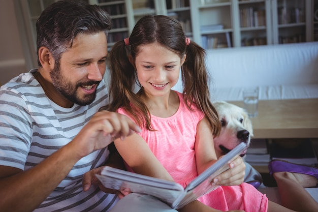 Smiling father and daughter looking at photo album in living room